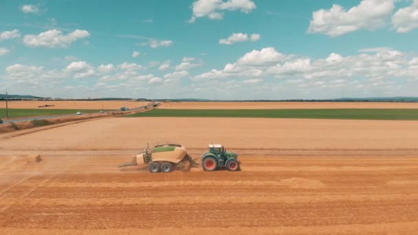 Légifelvételek repül búza mező és autópálya út felső részén a kombájn és a traktor-pótkocsi, ami búza halom nyári napon 4k.