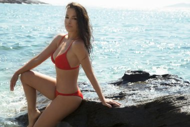 beautiful young woman in red bikini standing by the sea, summer day portrait