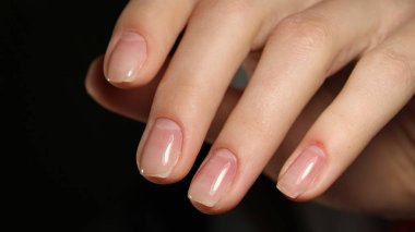 gentle natural female hands natural nail varnish on a dark background