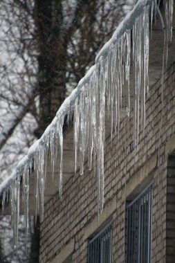 icicles hanging from the roof of a brick house