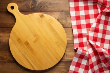 cutting board and tablecloth at wooden table surface, top view