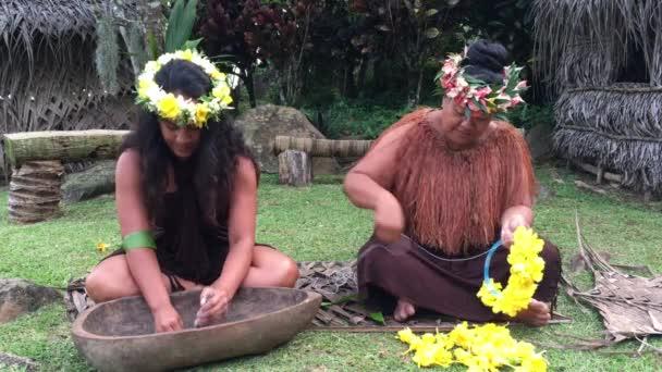 Két óceániai nők működik szabadtéri egy Maori falu, a Felvidéken Rarotonga, Cook-szigetek.