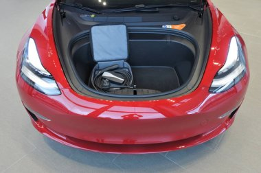 The front bonnet storage space and electric cable of the plug-in electric car Tesla Model 3, a mid-size / compact executive luxury four-door sedan manufactured and sold by Tesla, Inc.
