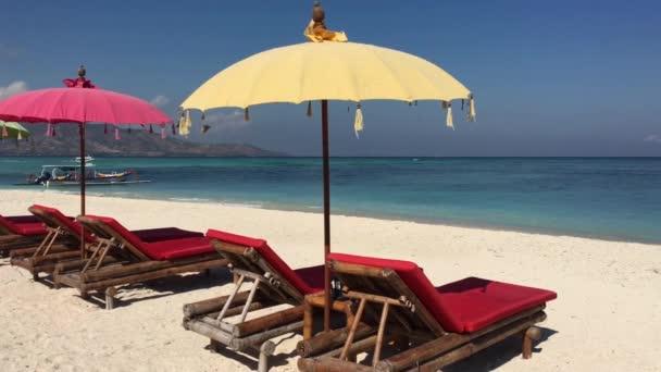 Barevné balijské slunečníky na pláži Gili Air Island jsou oblíbenou turistickou atrakcí mezi ostrovy Bali a Lombok, Indonésie.