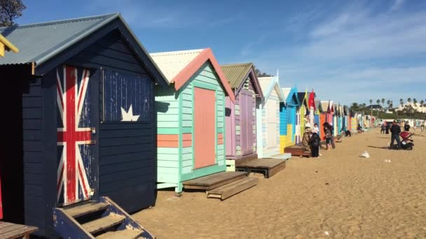 MELBOURNE - MAR 15 2019:Visitors at Victorian bathing boxes in Brighton beach Melbourne Victoria Australia, an Iconic group of 82 brightly colored wooden beach huts from the early 1900s.