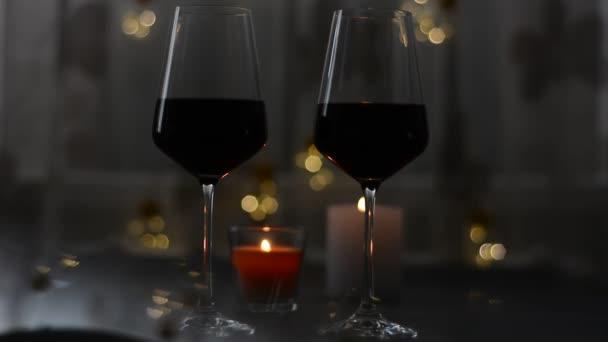 zwei Gläser Rotwein stehen auf einem dunklen Tisch mit Kerzen und Girlanden
