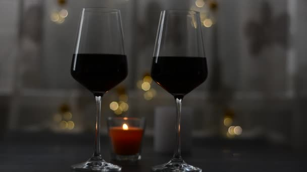Two glasses of wine red standing on a dark table with candle and garlands