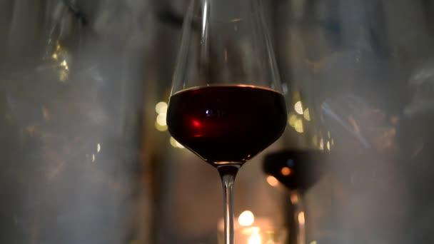 Dvě sklenky vína červená stojícího na tmavý stůl s svíčku a girlandy