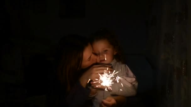 Happy mother and her daughter and Bengal fire at night. Mother holding sparkler, then she  kissing child while he looking at light which going out at the end