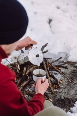 Traveling man a sits near camp fire an in winter time and pours itself hot coffee . Concept adventure active vacations outdoor. Winter camping