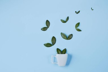 Creative composition. Coffee cup with birds made of natural green leaves on blue background. Flat lay, top view, copy space. Coffee and Nature concept.