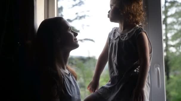 liebevolle Mutter lacht streichelt rührende Nasen mit süßer Tochter, die am Fenster sitzt, glückliche Mutter und kleines Kind, die sich umarmen und Spaß beim Spielen haben, genießen lustige Momente gute Zeit miteinander