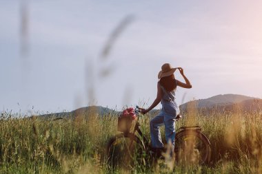 Rear view shot of woman outdoor with vintage bicycle and a basket of flowers and enjoying sunset against the background of the mountains. Active vacation concept. People and lifestyle.