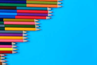 Back to school concept. Closeup images of many color pencils isolated on blue background. Creative flat lay, top view, copy space.