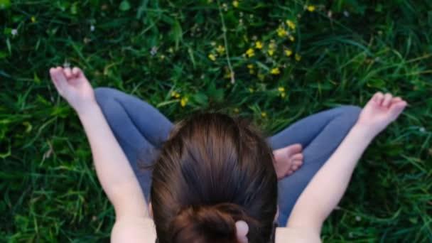 Venku je mladá žena jóga, uklidněte se a Meditujte, když cvičíte jóga, abyste prozkoumali vnitřní mír, cvičením ardha padmasana, napůl lotosové pozice s gestem mudrá. Dobrá koncepce