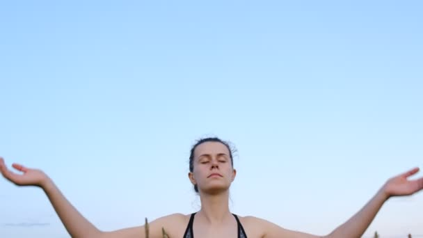 Young woman practicing yoga,  working out, wearing sportswear, with ponytail enjoying fresh air outdoor, relaxing with eyes closed, feeling alive, breathing, dreaming, rear view. Healthy and Yoga Concept
