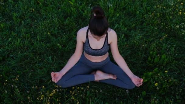 Junge sportliche Frau, die Yoga praktiziert, Ardha Padmasana-Übung macht, Halb Lotus-Pose mit Mudra-Geste, Training, Sportbekleidung, im Naturhintergrund. Wohlfühlkonzept