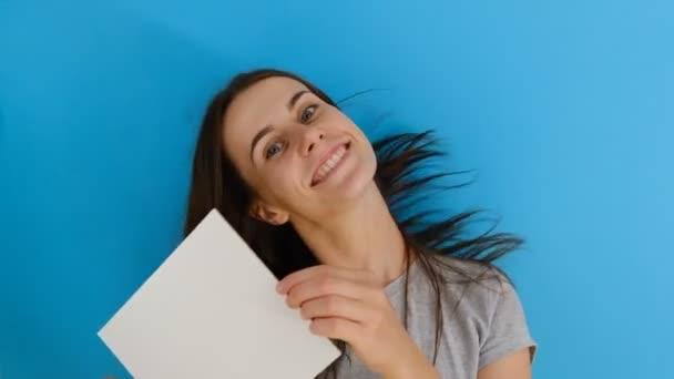 Portrét krásné usměvavé ženy s dlouhými vlasy potřásající hlavou, držící prázdný list papíru izolovaný nad modrým pozadím s kopírovacím prostorem. Lidé upřímné emoce životní styl.