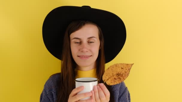 Positive European girl holds mug of drink, dressed in blue sweater and black hat, enjoys spare time, drinks hot coffee in before autumn walk, models against yellow background.