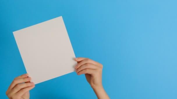 A kék háttérrel elkülönített, üres papírt tartalmazó női kezek másolási területtel.