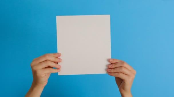 Testbeszéd koncepció. Az üres papírlapot elszigetelten tartó női kezek a kék hátterű, másolási térközzel történő jóváhagyást vagy megegyezást mutatják be. Kézjel. Hasonló kézmozdulat