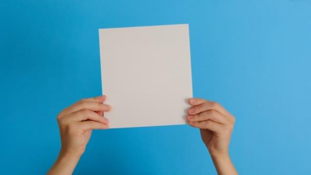 Az üres papírlapot elszigetelten tartó női kezek a kék hátterű, másolási térközzel történő jóváhagyást vagy megegyezást mutatják be. Testbeszéd koncepció. Kézjel. Hasonló kézmozdulat