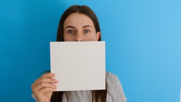 Closeup portrét nádherné usmívající se ženy, která drží prázdný list, znázorňuje schválení nebo souhlas na modrém pozadí s prostorem pro kopírování. Pojetí jazyka textu. Značka ruky. Podobné gesto