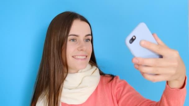 Portré gyönyörű lány mosolyog, úgy selfie portré a mobiltelefonján, élvezte a szabad idő, teszi képek a szociális hálózatok, stílusos kendő és rózsás jumper, mosolyog a kamera, elszigetelt több mint kék háttérképet