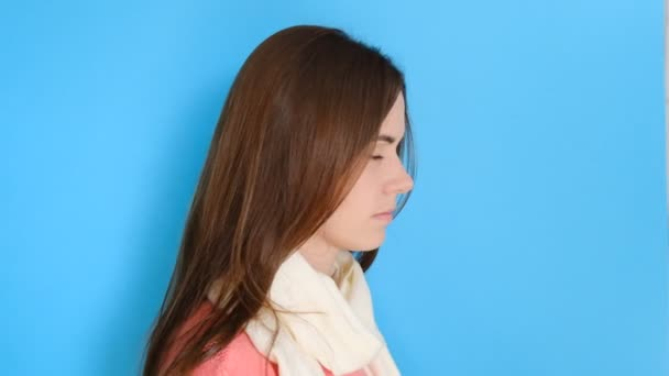 Portrait of serious lovely woman, looks stern at camera and wraps in scarf, has hands crossed over chest, models over blue wall