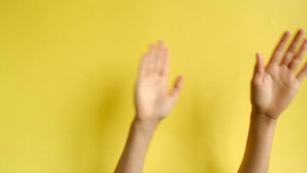 Unerkennbare weibliche Hände winken zu Musik-Rhythmus-Geste auf gelbem Hintergrund im Studio. Körpersprache. Werbefläche, Arbeitsplatz-Attrappe.