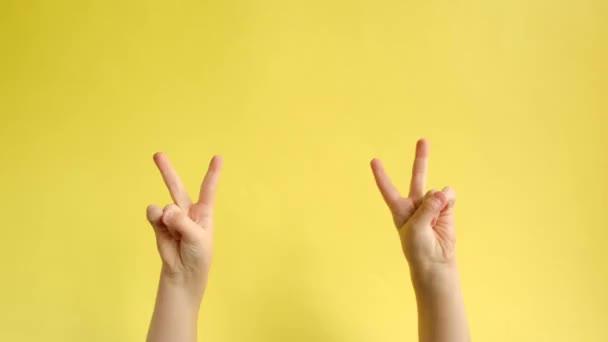 Closeup dětských rukou ukazuje nápis victroy na žlutém papíře, vyjadřuje oslavu a triumf. Pojetí jazyka textu. Značka ruky. Rozbíjení papírové zdi.