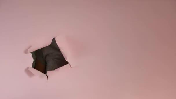 Frauenhand zeigt auf Kopierraum durch zerrissenes Loch in rosa Papier und zeigt Daumen. Körpersprache. Handzeichen. Papierwand durchbrochen.