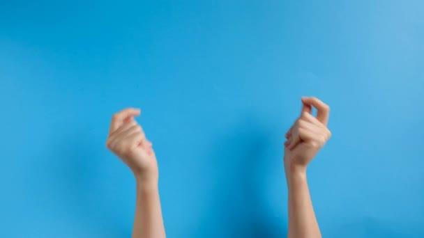 Frauenhände schnipsen ihre Finger zu Musik-Rhythmus-Geste auf blauem Hintergrund im Studio. Körpersprache. Werbefläche, Arbeitsplatz-Attrappe.