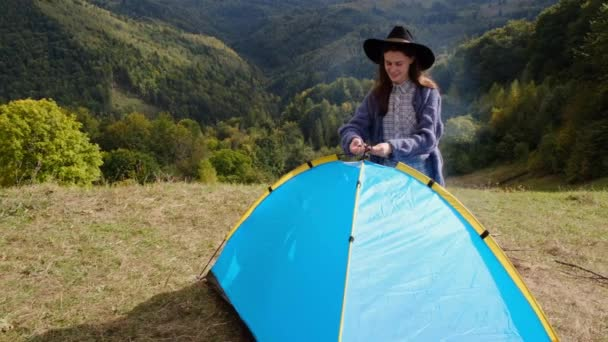 Tourist or traveller on hiking trip sets up camp, futuristic camping tent on mountains landscape. Girl in scenic landscape enjoying vacation travel adventure nature. Concept outdoor activities