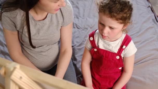 Seitenansicht der schwangeren jungen Mutter lehrt süße Vorschultochter, auf der Tafel zu schreiben, während sie zu Hause im Bett sitzt, Familienerziehung zusammen. Frühkindliche Entwicklung.