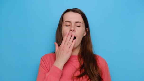 Álmos fiatal nő ásít, álmosító figyelmetlen, álmosnak érzi magát, unatkozik, alváshiányban szenved, pulóvert visel, elszigetelve a kék stúdió hátterében. Fáradtság és ébredés koncepció