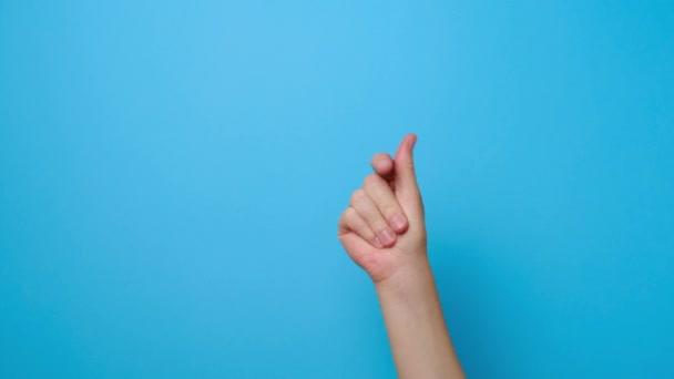 Nahaufnahme einer weiblichen Hand, die rhythmische Melodie spielt und die Finger schnappt, isoliert auf blauem Studiohintergrund mit Kopierplatz für Werbung.