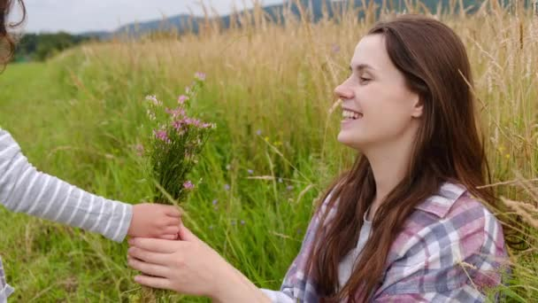 Cute little child daughter congratulating happy mom, presenting field flowers, embracing affectionate mum having fun sit on grass among meadow. Concept of family relationships and nature recreation