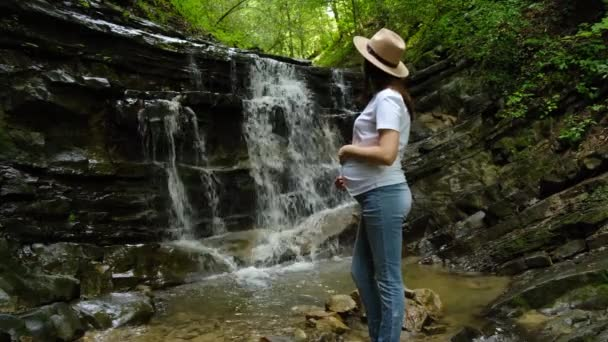 Pregnant woman in hat standing near beautiful mountain waterfall, look at powerful mountain water stream, enjoy nature. Quiet place for green tourism. Concept world traveller or blogger, wanderlust