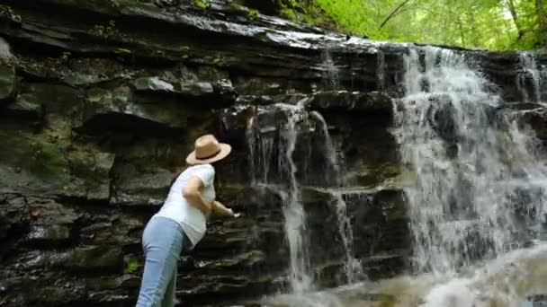 Cheerful young pregnant woman in hat enjoy mountain waterfall, touching fresh stream water in nature. Happy cute future mom enjoys a weekend. Amazing concept of exploring great outdoors