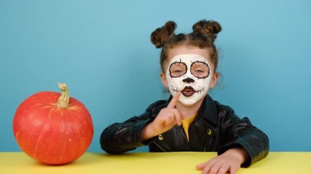 Gesichtskunst und traditionelles mexikanisches Urlaubskonzept. Kleines Mädchen, das neben einem Kürbis sitzt, den Zeigefinger an den Lippen hält und um Schweigen bittet, trägt im Halloween-Kostüm Zuckerschädel-Make-up