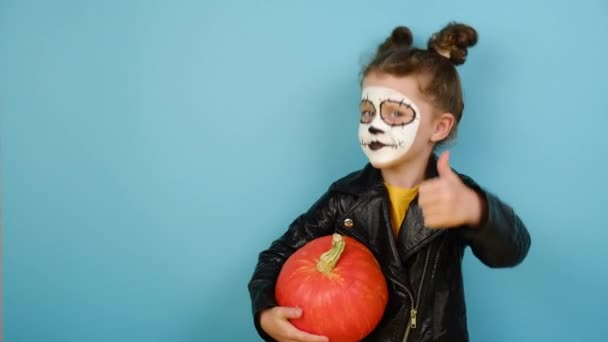 Kindermädchen hat ein Gesicht, das arg an Totenköpfe erinnert, hält orangefarbenen Kürbis in der Hand, zeigt Zeichen ok, trägt schwarze Lederjacke, isoliert auf blauem Studiohintergrund mit Kopierraum. Happy-Halloween-Konzept