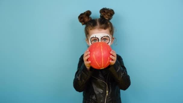 Schockiertes kleines Mädchen trägt beängstigendes Make-up, blickt zur Seite und versteckt sich hinter einem Kürbis, bekleidet mit schwarzer Lederjacke, isoliert auf blauem Studiohintergrund mit Kopierraum. Happy-Halloween-Konzept