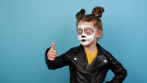 Kleines Mädchen hat kreatives buntes Gesicht, Daumen hoch Geste, zeigt Erfolgszeichen, isoliert auf blauem Hintergrund, gekleidet in Halloween-Kostüm, trägt Zuckerschädel Make-up. Todestag in Mexiko-Stadt