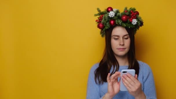 Roztomilá žena používající mobilní telefon, hledící stranou body na prázdné místo, nosí smrk sváteční věnec kolem hlavy a modrý svetr, stojí na žlutém pozadí. Šťastný Nový rok veselé prázdniny koncept