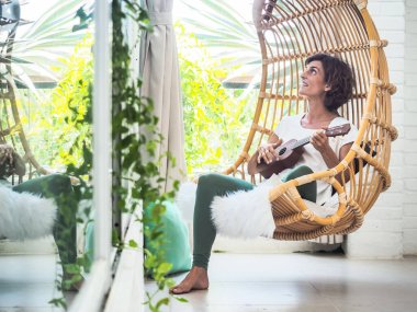 young woman playing ukulele sitting in swing chair, relax and vacation concept