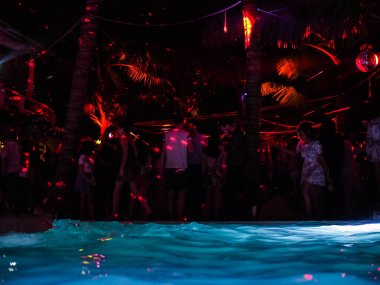 blurred group of people dancing near swimming pool at the night