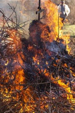 Yanan ateş. Shrovetide içinde büyük şenlik ateşi. Yanan ağaç dalları. İnsanlar ateşe bak. Pagan ayin baharın gelişini adanmış.