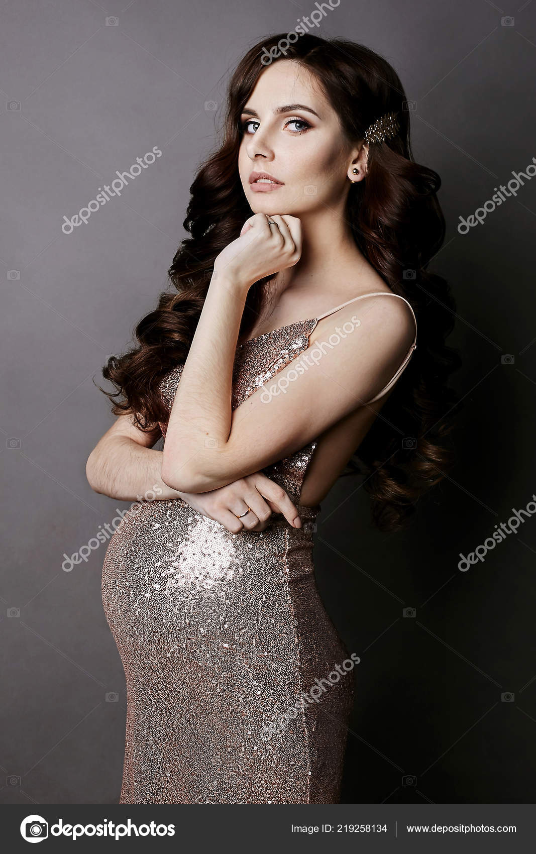 eb2c6014cd20c Fashionable and pregnant brunette model girl with gentle makeup, in the  dress with gold sequins