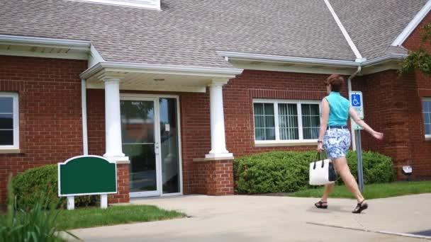 Frau betritt Bürogebäude am Morgen